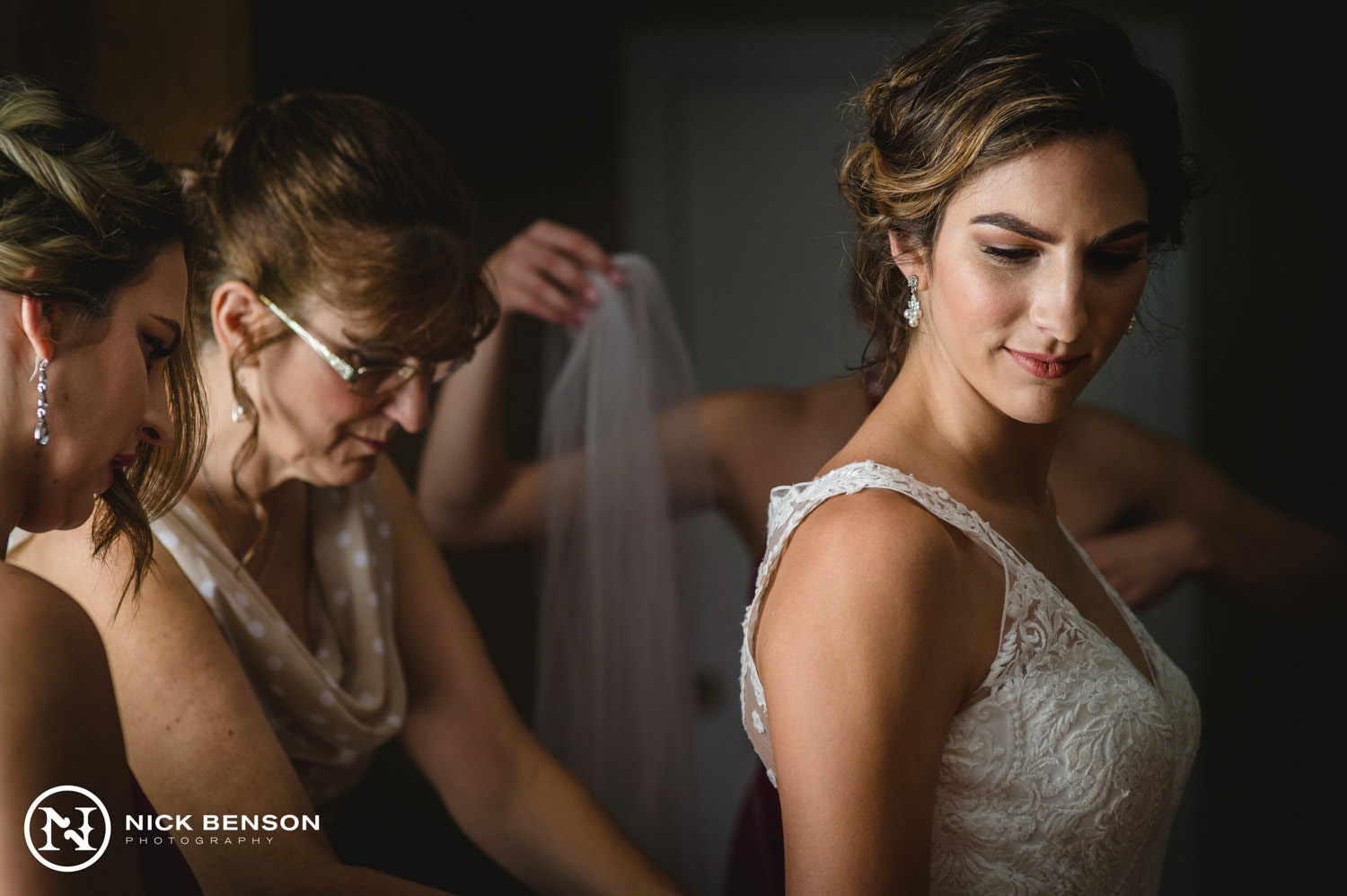 bride and bride's mother putting on wedding dress