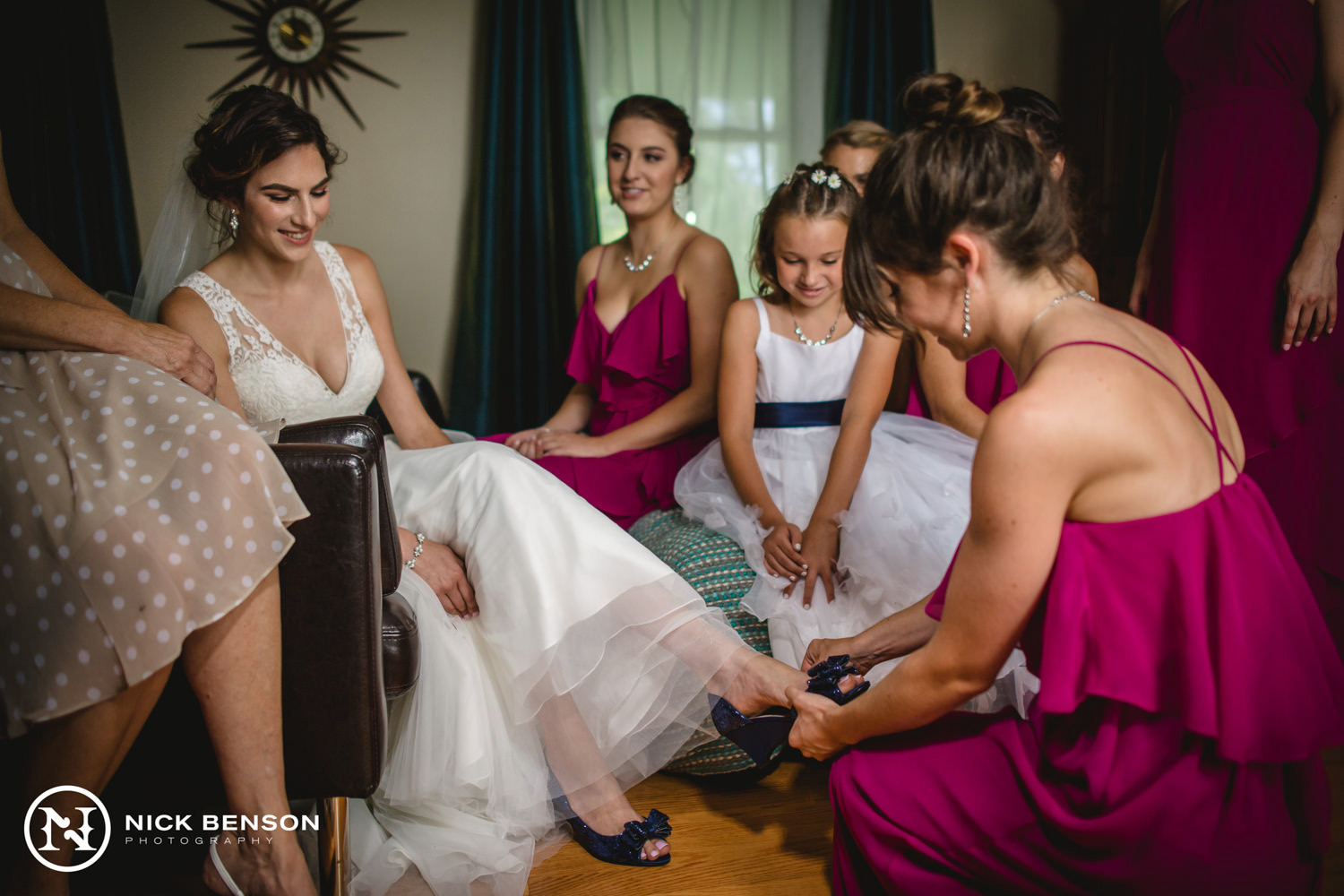 bridesmaids helping bride put shoes on